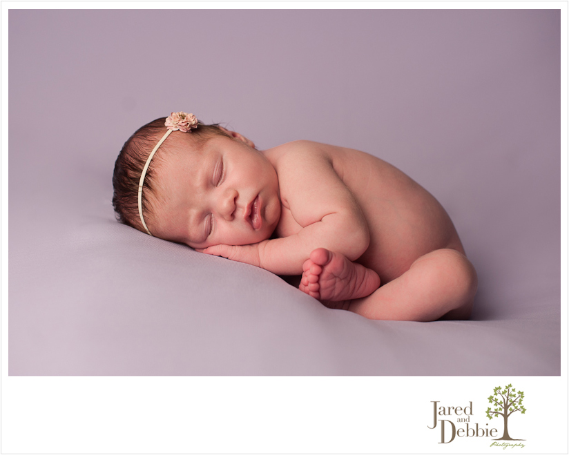 Baby girl on purple in newborn session with Jared and Debbie Photography