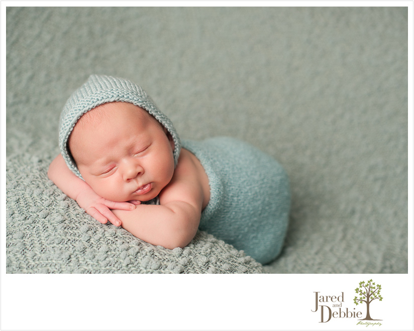 Newborn baby boy on blue during session with Jared and Debbie Photography