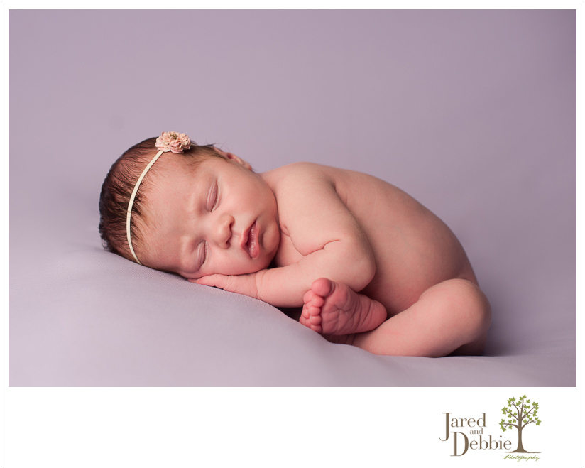 Newborn baby on Purple during photography session with Jared and Debbie