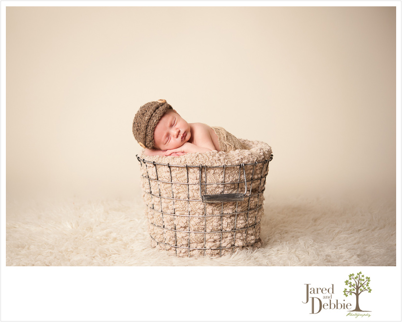 newborn baby boy in basket during session with Jared and Debbie Photography