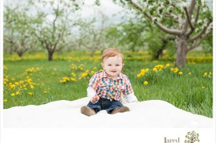 10 month old baby at apple orchard during session with Jared and Debbie Photography