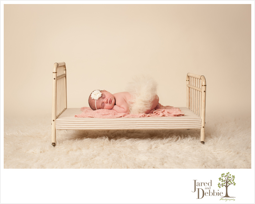Newborn Baby girl in tutu on vintage bed during session with Jared and Debbie
