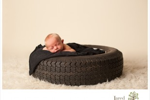 Newborn boy in tire during session with Jared and Debbie