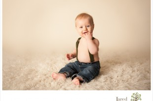 Baby boy with suspenders and jeans at 6 month session with Jared and Debbie