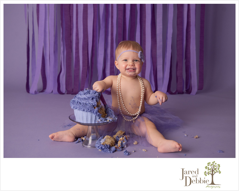 Baby girl in purple and pearls during cake smash session