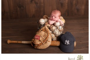 Newborn Baby Boy in baseballs Jared and Debbie Photography